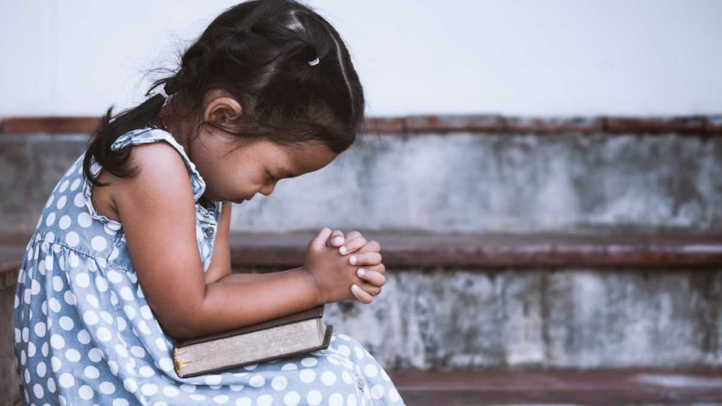 child praying for success in exam